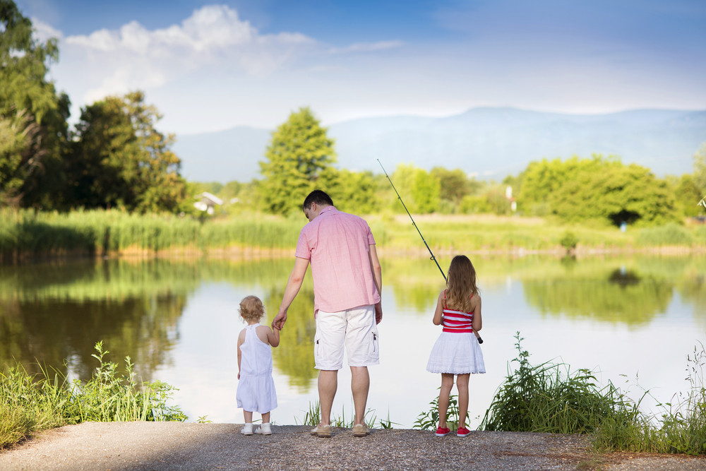 Happy young father fishing on the lake with his little daughters