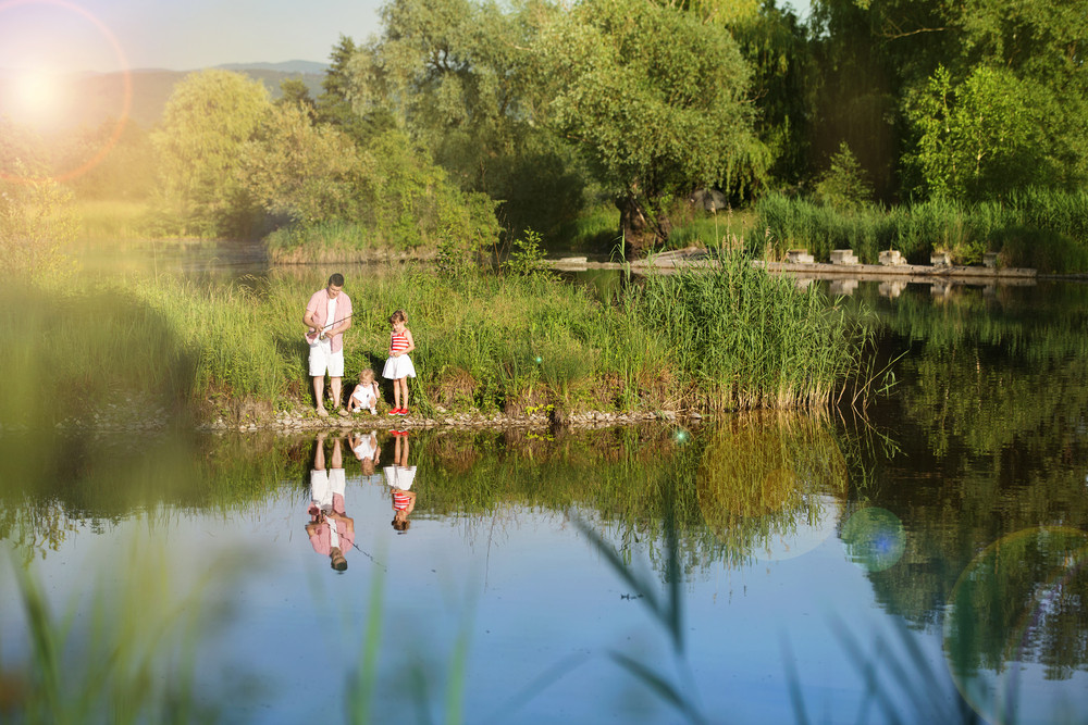 Happy young father fishing on the lake with his little daughters, reflecting in the water
