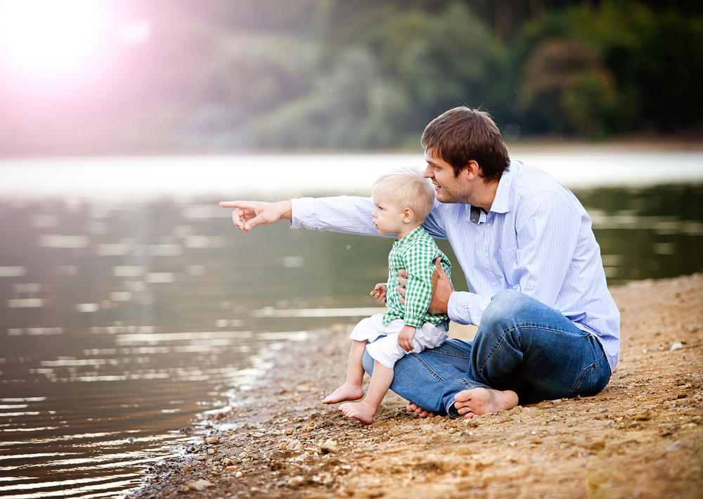 Happy young father spending time together with his little sonby the lake on the sandy beach