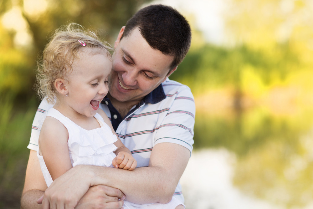 Happy young father spending time with his little daughter in green nature.