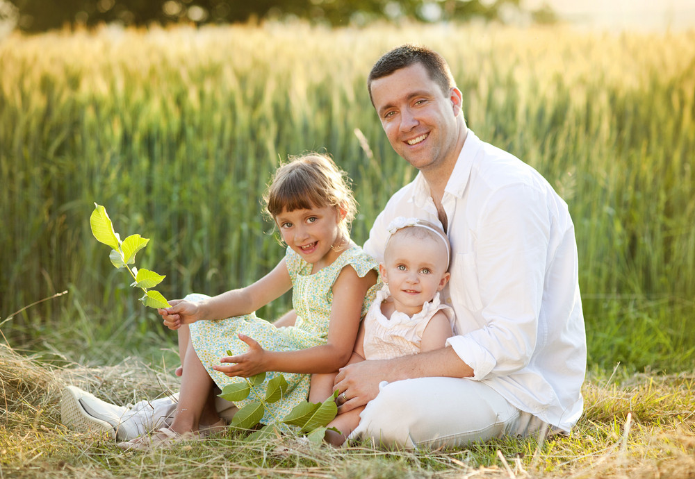 Happy young father spending time with his little daughters in green nature.