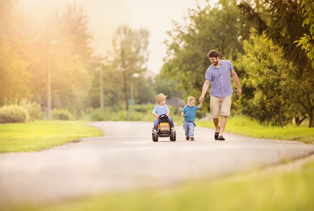 Happy young father with his two little sons have fun on road, one boy is riding on little tractor, other boy is holding father's hand