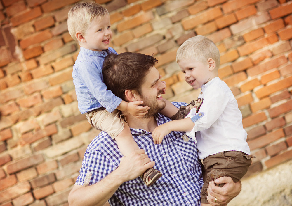 Happy young father with his two little sons have fun together in nature by the old brick house