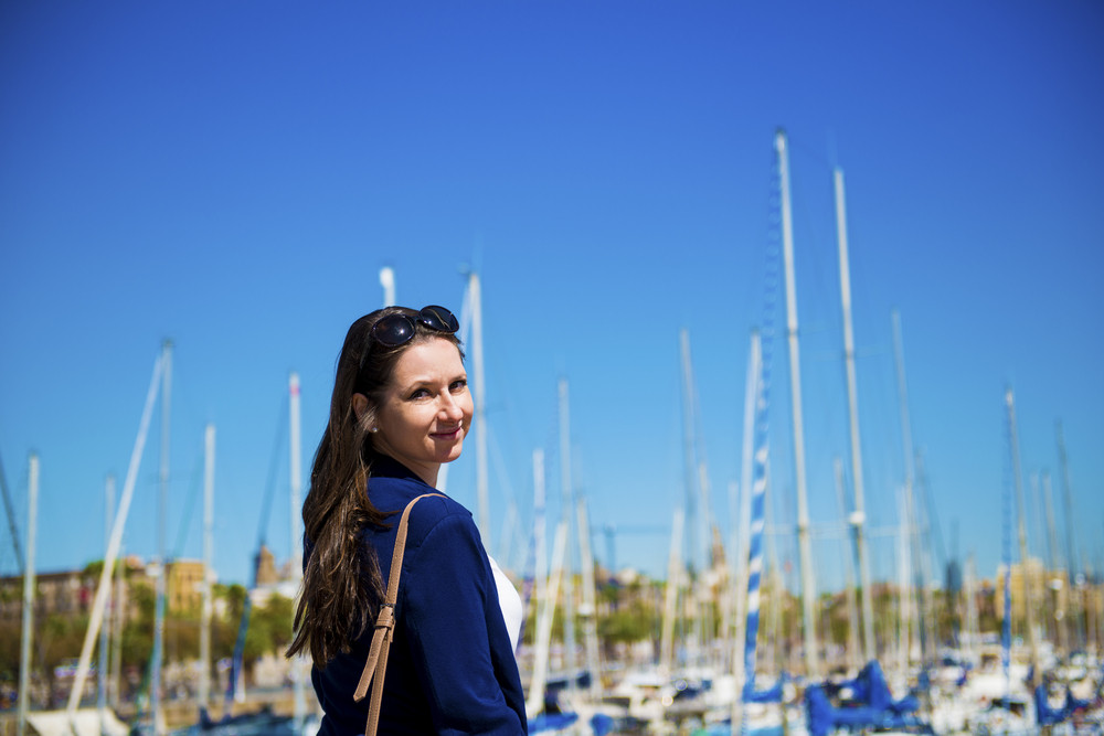 Happy young female tourist at the boat harbor