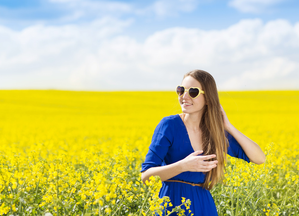 Happy young girl in blue dres nad sunglasses enjoying free time in yellow colza field