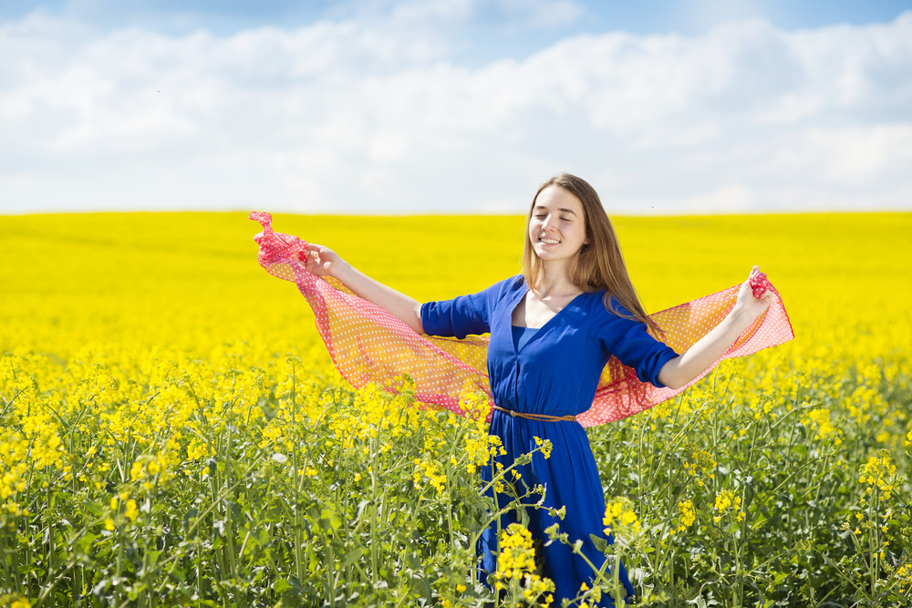 Happy young girl in blue dress and red scarf enjoying free time in yellow colza field