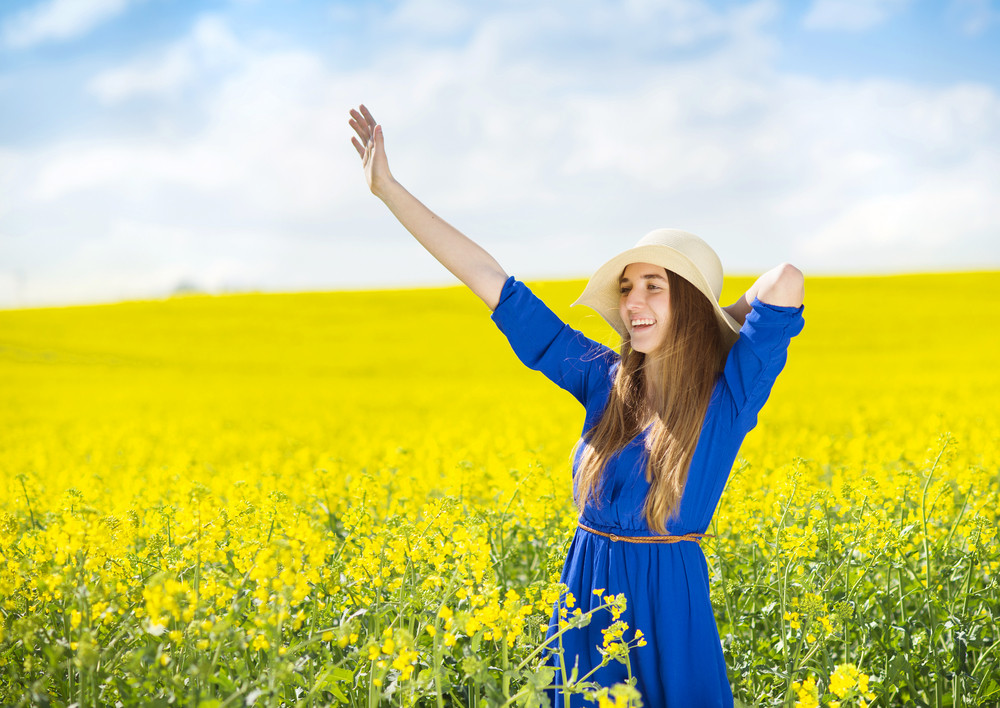 Happy young girl in blue dress and straw hat enjoying free time in yellow colza field