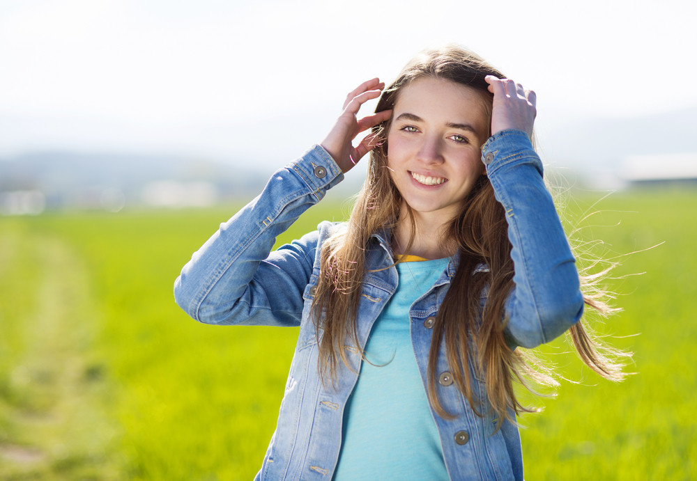 Happy young girl in blue jeans jacket enjoying free time in green field