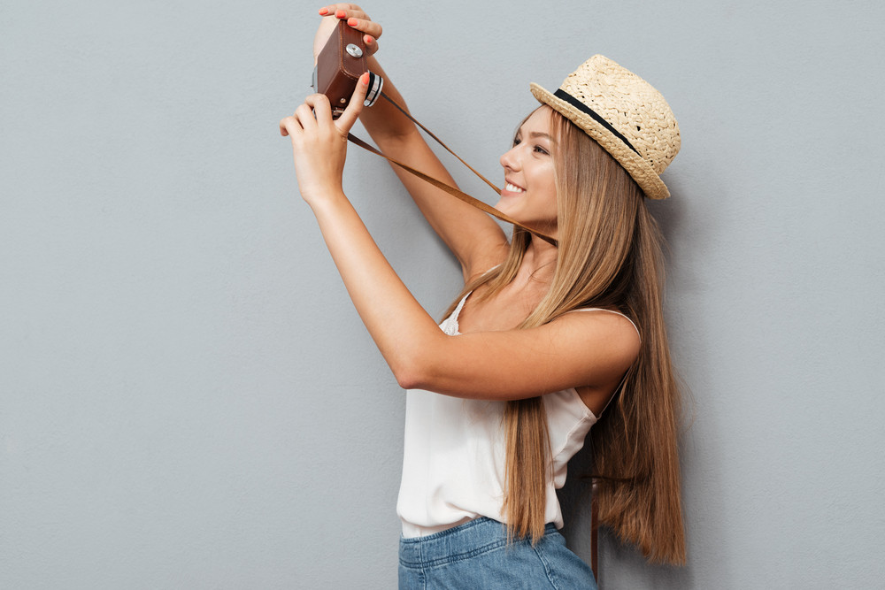 Happy young girl in hat making selfie with retro camera isolated on a gray background