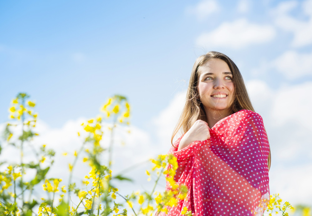 Happy young girl with red scarf enjoying free time in yellow colza field