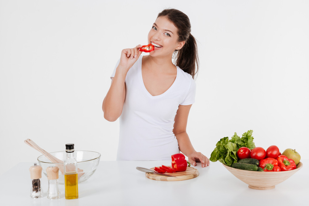 Happy young lady dressed in white t-shirt cooking with vegetables while eating them. Isolated on white background.