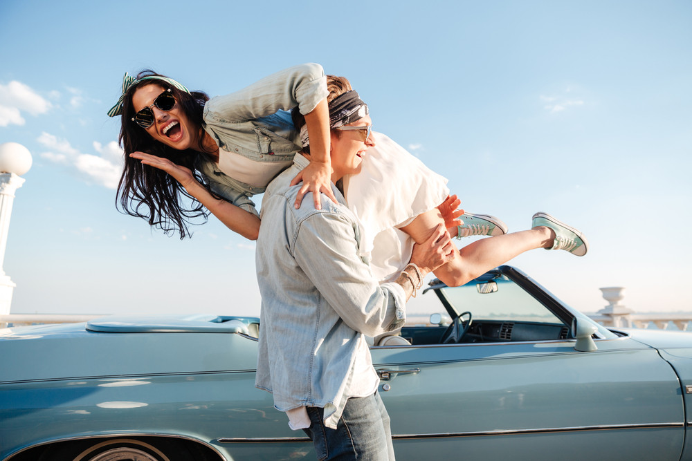 Happy young man carrying his woman and laughing near vintage car
