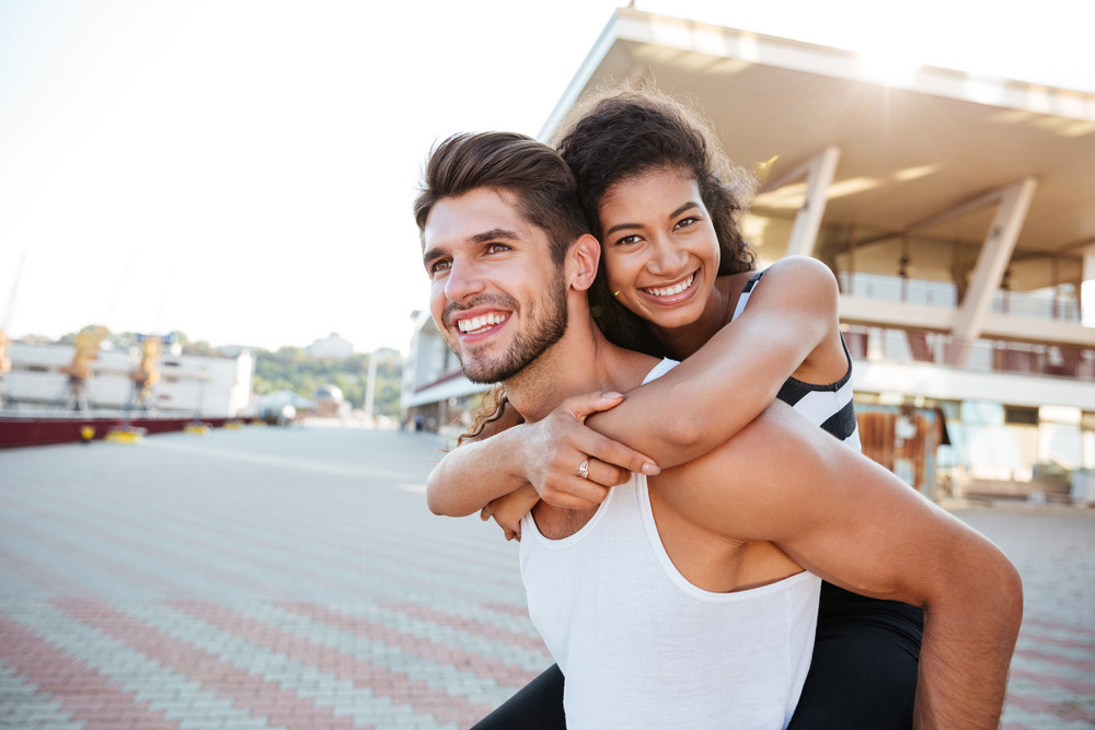 Happy young man giving her girlfriend piggyback ride outdoors