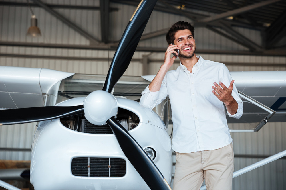 Happy young man standing and talking on mobile phone near the plane