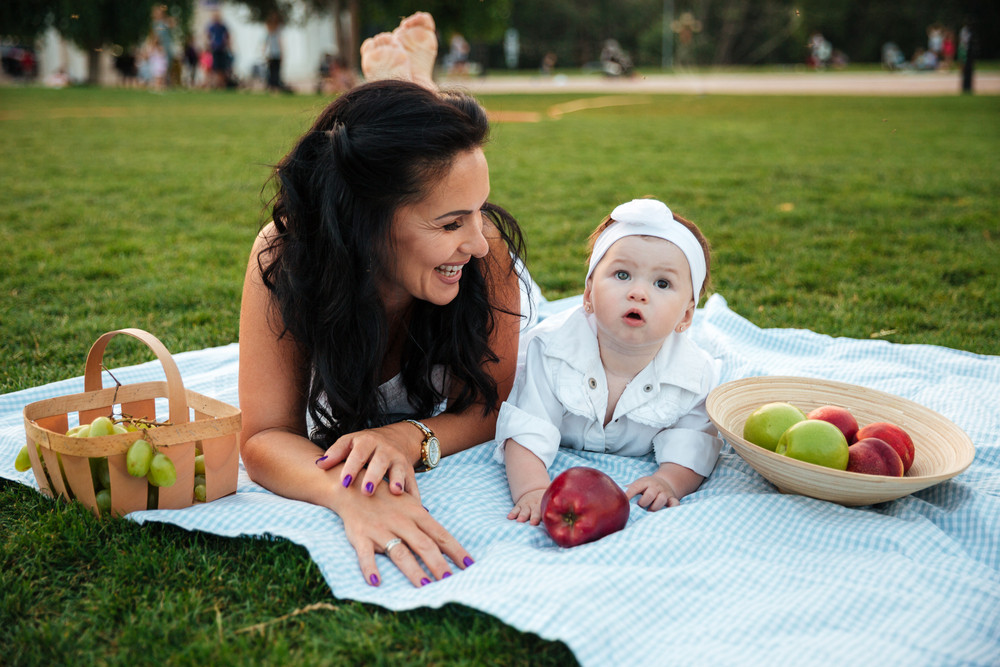 Happy young mother and her little daughter lying and laughing on picnic