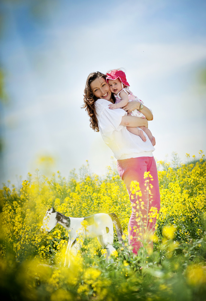Happy young mother having fun with her baby daughter in summer nature