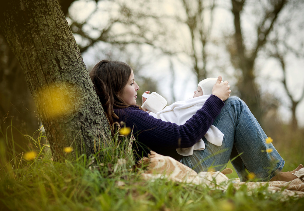 Happy young mother holding her newborn baby boy in nature