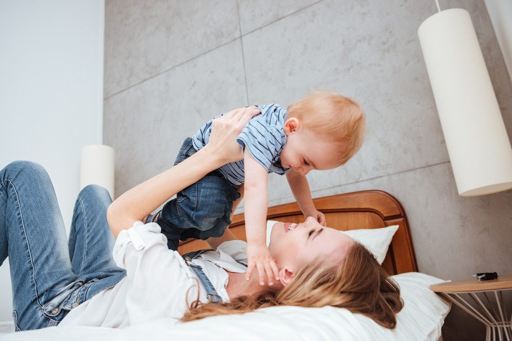 Happy young mother playing and having fun with her little son on bed at home
