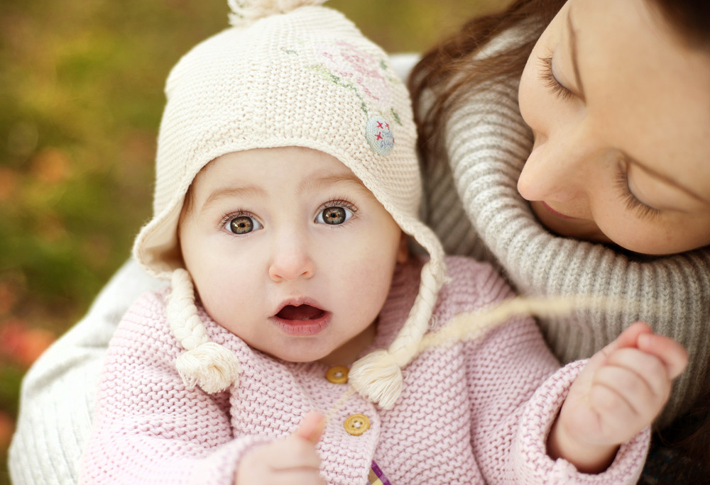 Happy young mother relaxing with her little daughter in golden and colorful autum nature