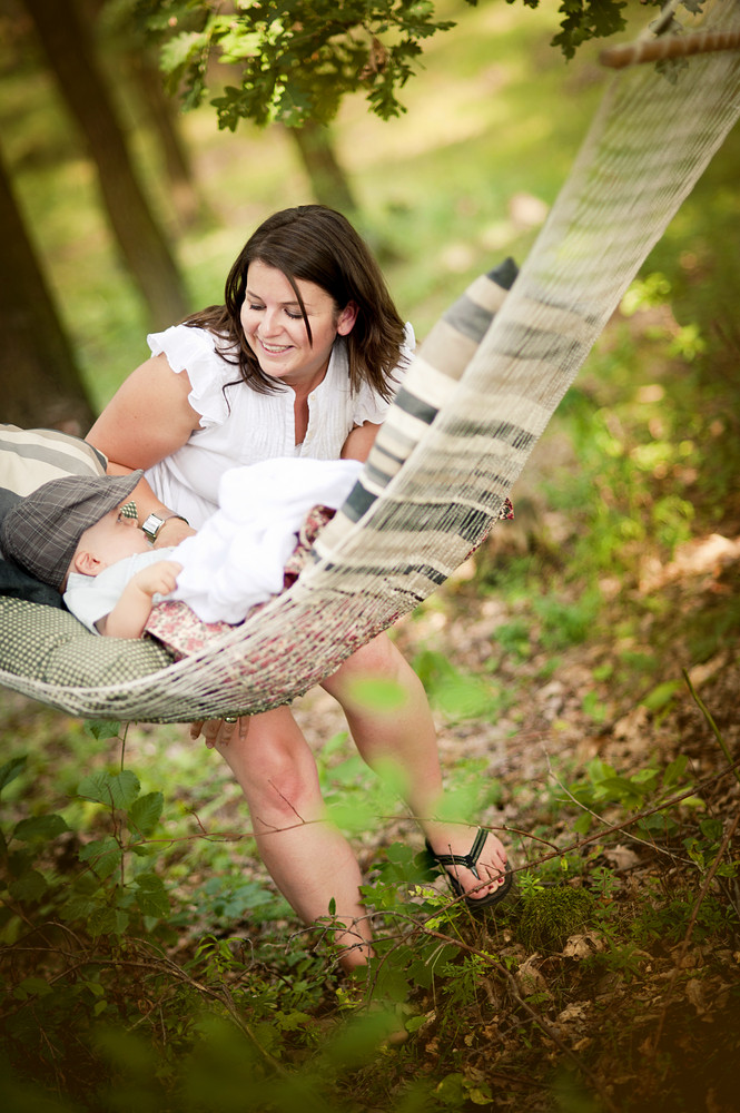 Happy young mother spending time with her baby son in green nature, little boy is lying in hammock