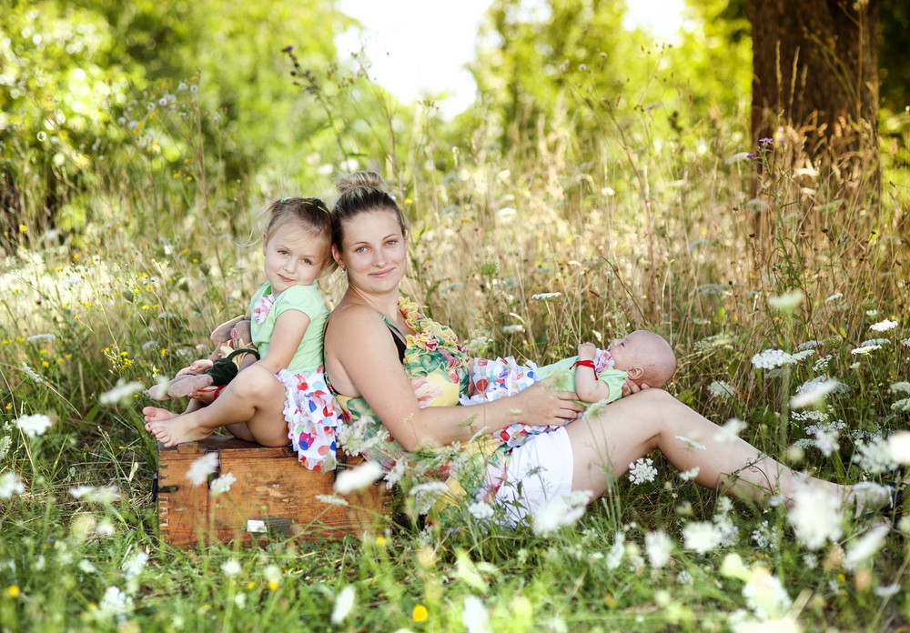 Happy young mother spending time with her little daughter in green nature.