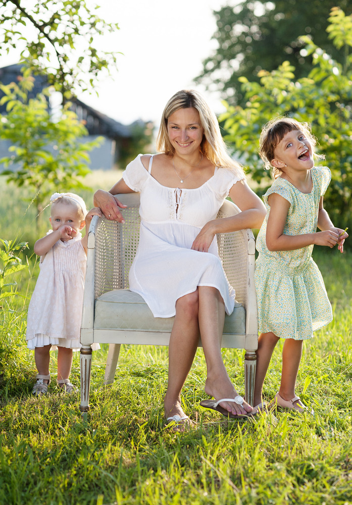 Happy young mother spending time with her little daughters in green nature.