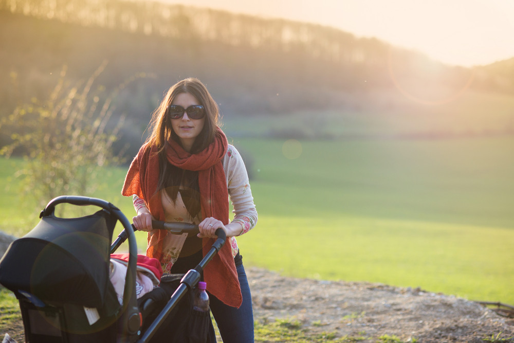 Happy young mother with pram during the walk in nature