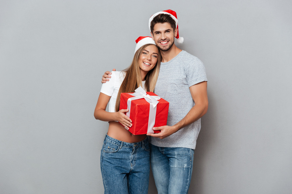 Happy young people with christmas gift. Smiling couple. gray background.