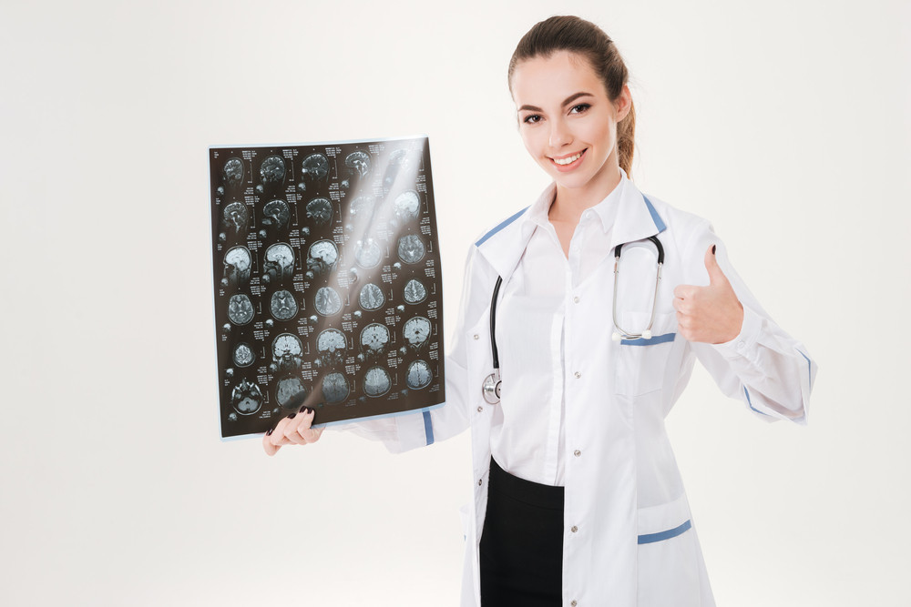 Happy young woman doctor holding radiography and showing thumbs up over white background
