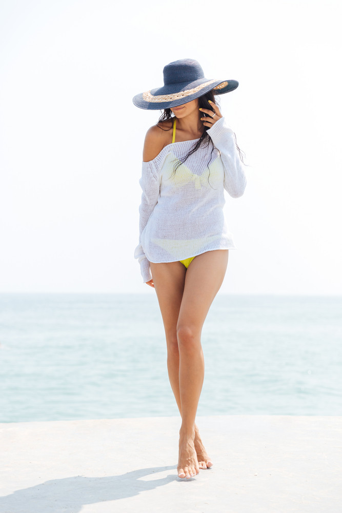 Happy young woman in bikini and beach hat at the beach