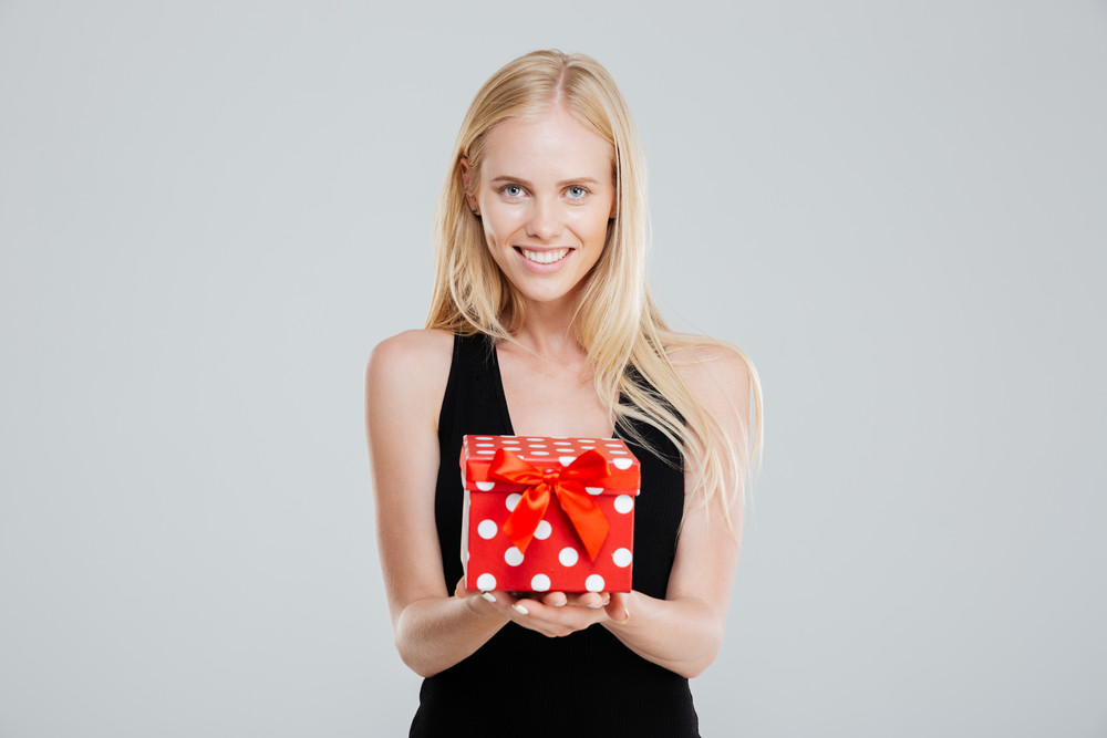 Happy young woman in black dress holding gift box isolated on a white background