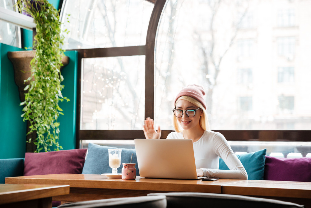Happy young woman in hat and glasses using laptop computer for video chat in cafe