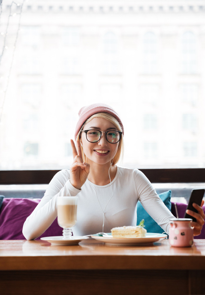 Happy young woman listening to music from cell phone and showing peace sign in cafe