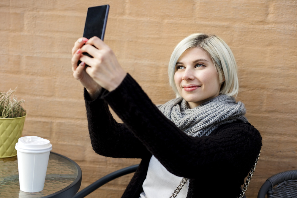 Happy Young Woman Taking Selfie At Sidewalk Cafe