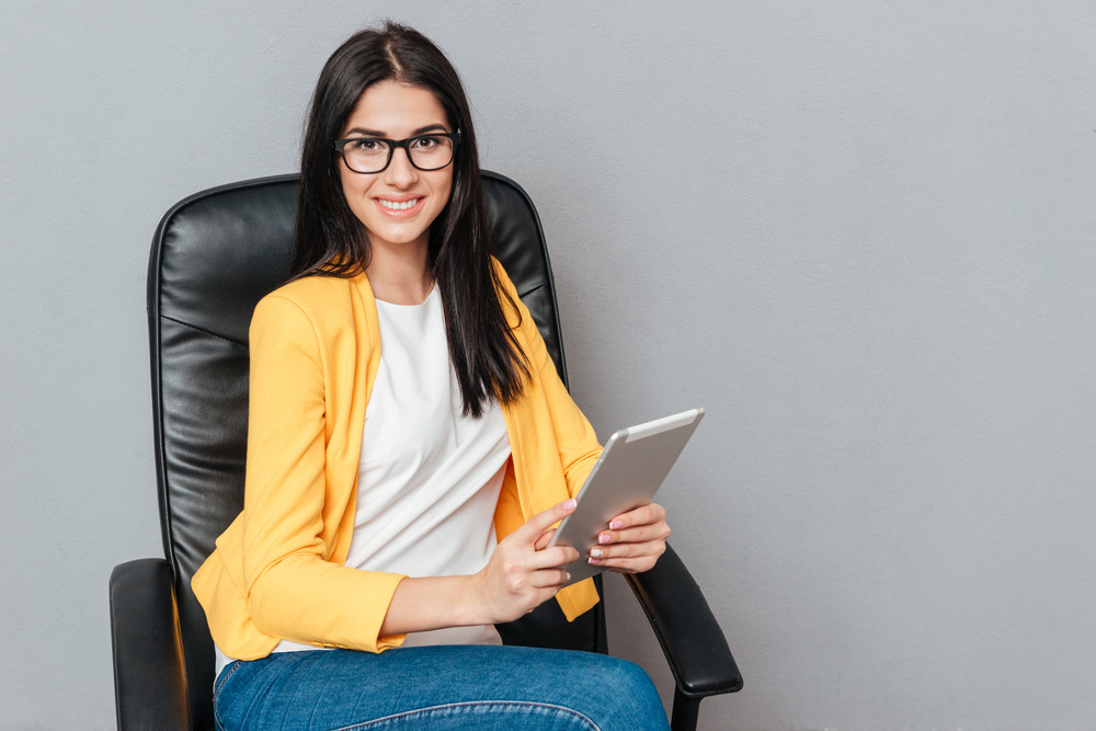 Happy young woman wearing eyeglasses and dressed in yellow jacket sitting on office chair while using tablet computer over grey background.