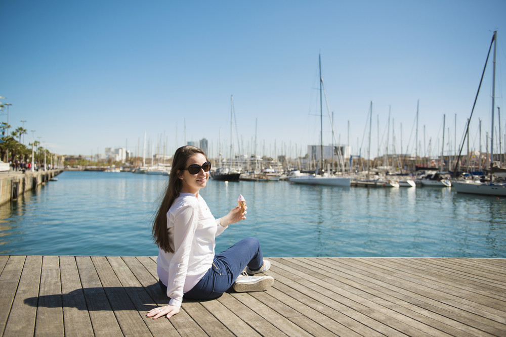 Happy young woman with ice cream is sitting on pier