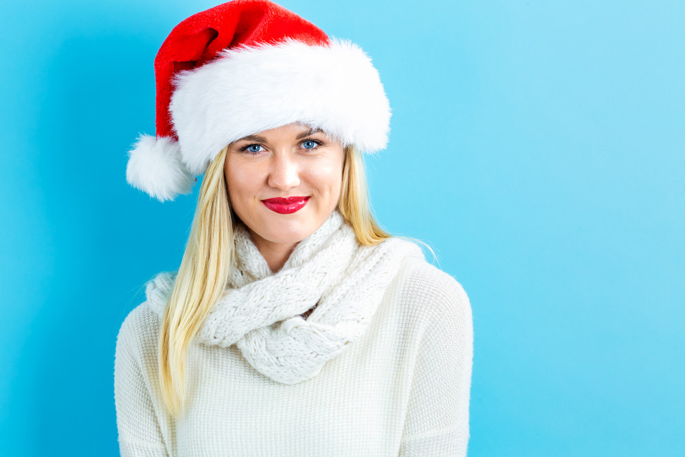 Happy young woman with Santa hat on a blue background