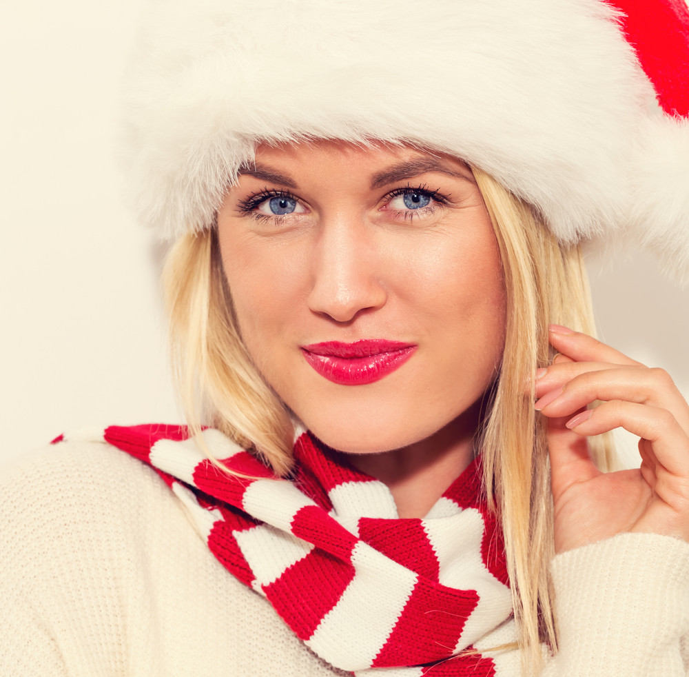 Happy young woman with Santa hat on a white background