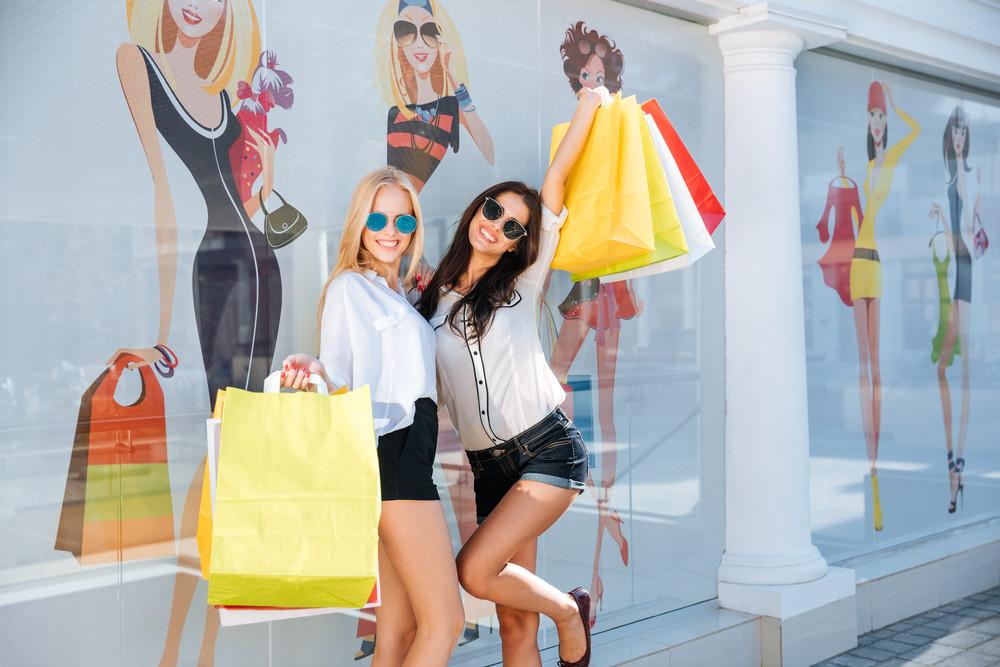Happy young women with shopping bags walking along city street and having fun