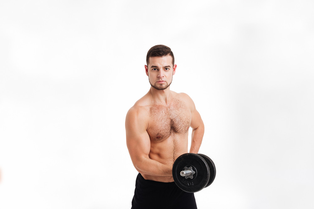 Healthy man with dumbbell. looking at camera