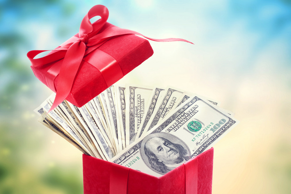 Heap of hundred dollar bills in a big red present box