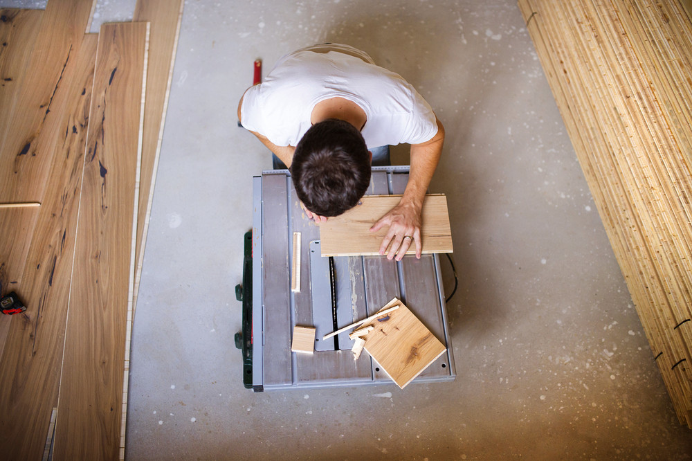 High angle view of handyman cutting plywood on circular saw in the new house