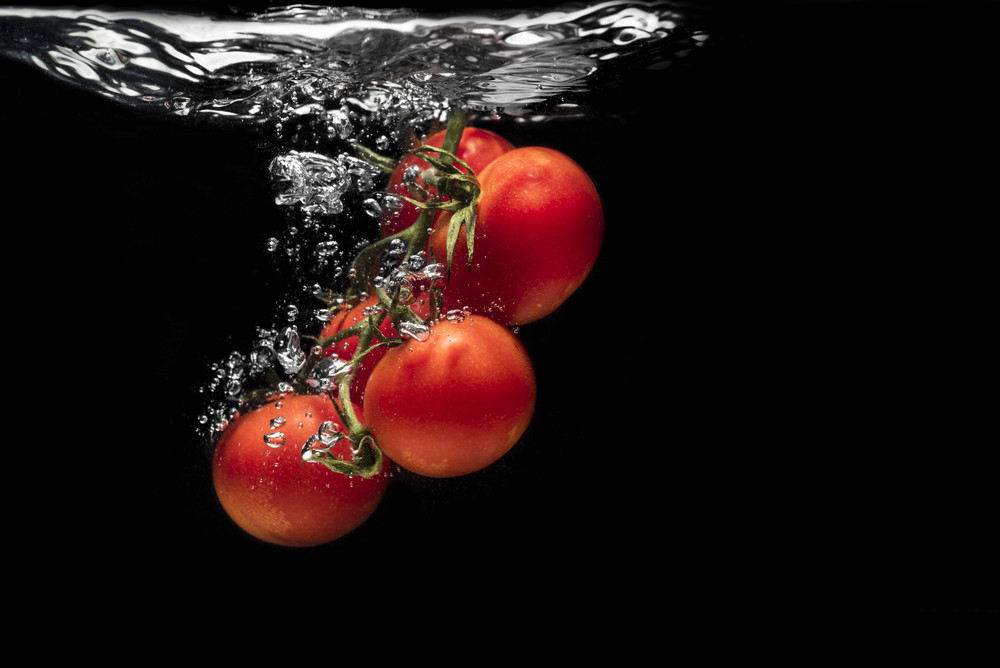High speed photography tomato splash in water isolated on the black background