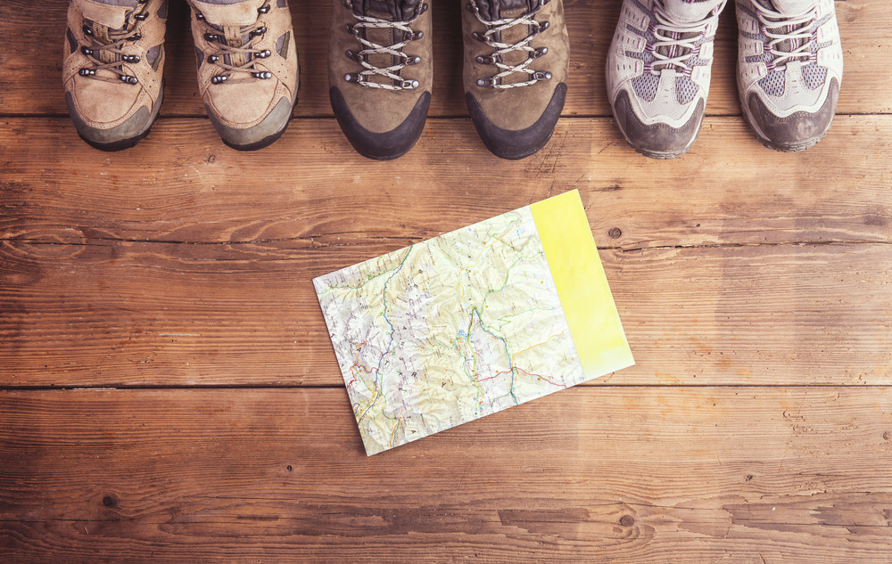 Hiking shoes and map laid on a wooden floor background
