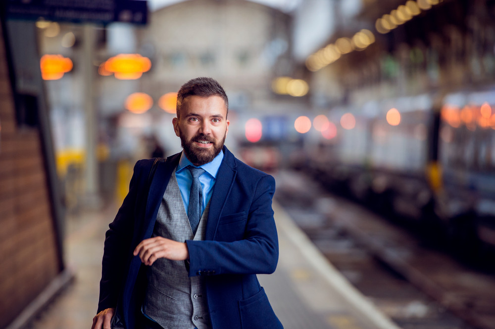 Hipster businessman at the staition running to catch the train