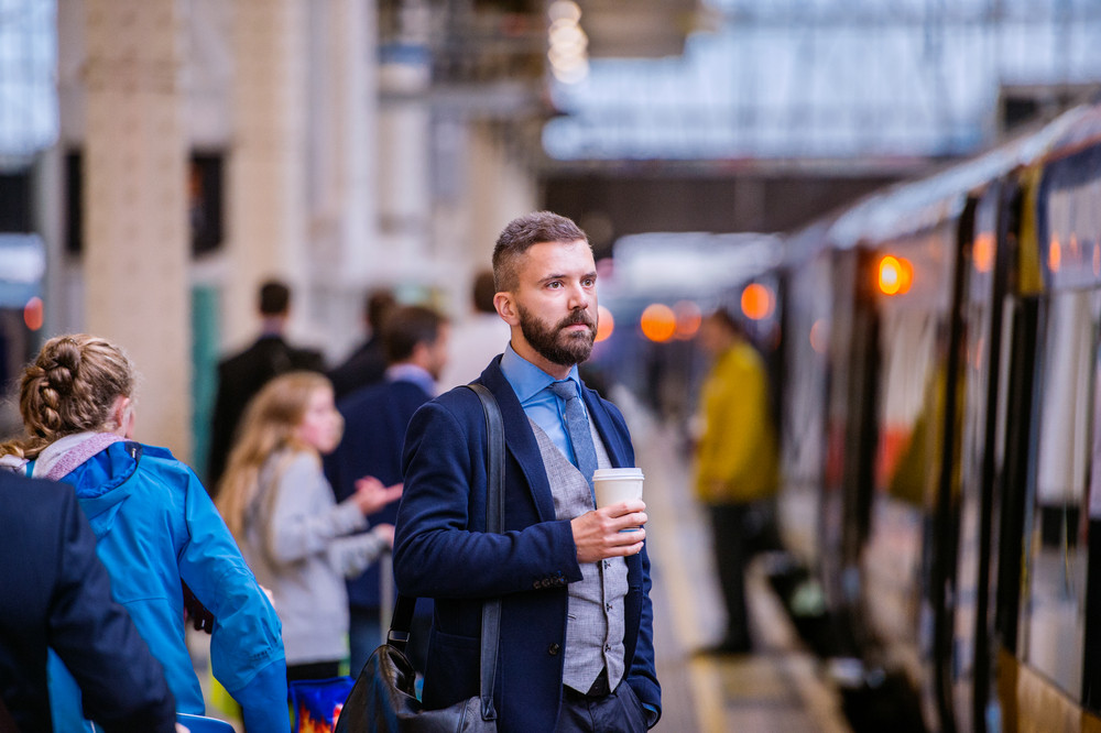 Hipster businessman holding a disposable coffee cup at the train station platform