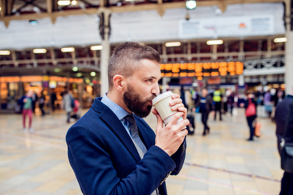 Hipster businessman holding a disposable cup and drinking coffee at the crowded train station
