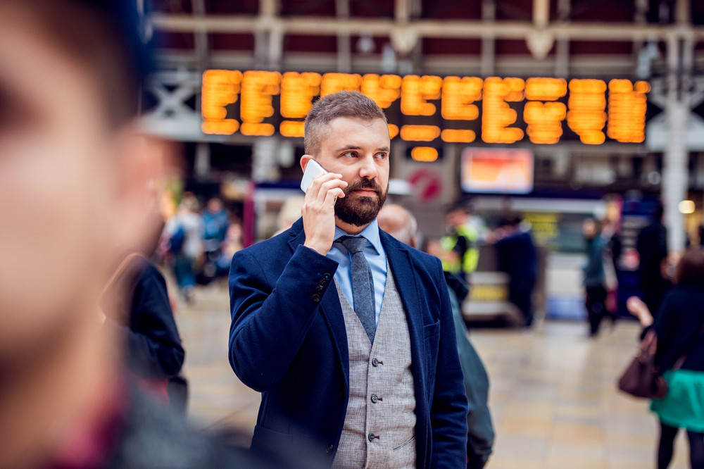 Hipster businessman holding a smartphone, making a phone call,  standing at the crowded station