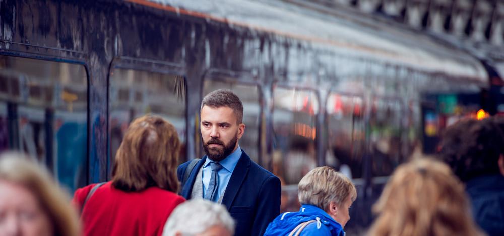 Hipster businessman walking at the station, crowded underground platform, train