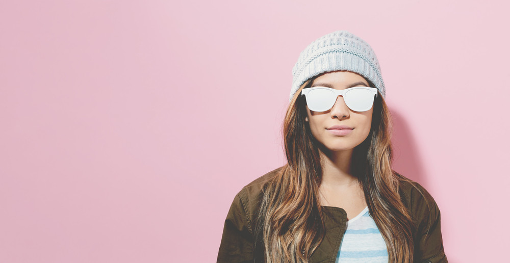 Hipster girl wearing sunglasses and hat on a pink background